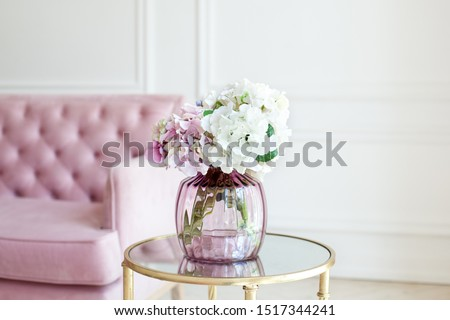 Bouquet of pastel hydrangeas in glass vase. Flowers in a vase at home. beautiful bouquet of hydrangeas is in a vase on a table near a pink sofa in a white living room. Home interior decor. Scandinavia #1517344241