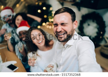 Joyous bearded male in white shirt holding glass with champagne and taking selfie with blurred friend in decorated for Christmas party room at home #1517352368
