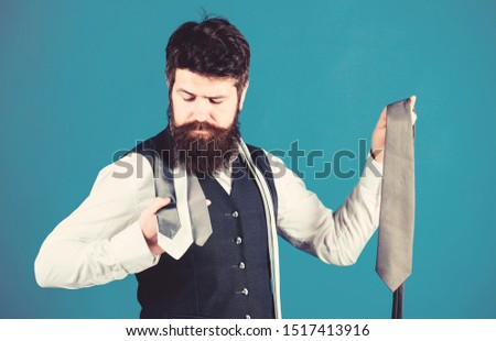 Perfect necktie. For formal occasions choose solid colored tie that is darker than your shirt. Match colors. Man bearded hipster hold few neckties on blue background. Guy with beard choosing necktie. #1517413916