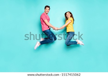Full length body size view of his he her she nice attractive friendly cheerful couple jumping up in air holding hands spending holiday isolated on bright vivid shine vibrant green turquoise background #1517415062