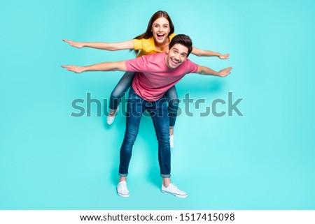 Full length body size view of nice attractive playful funny cheerful cheery couple guy carrying girl having fun like flying isolated over bright vivid shine vibrant green turquoise background #1517415098