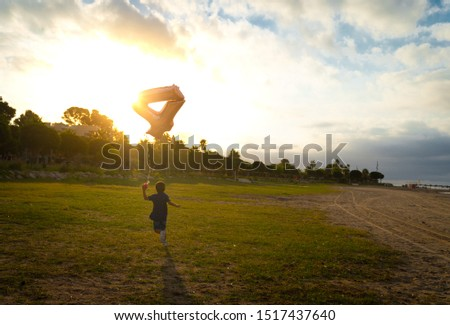 Happy birthday boy with a 4 years old balloon running towards the sunset in an open field #1517437640