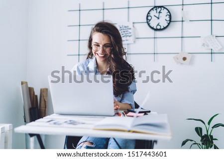Attractive pleased dark haired female in casual clothes and glasses concentrating on screen and typing on laptop while sitting at desk against white wall with black decor and clock in light apartment #1517443601