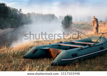 Fishing at dawn on a small river with fog over the water. On the shore is an inflatable rubber boat for fishing, fishing rods, a man fishing. #1517501948