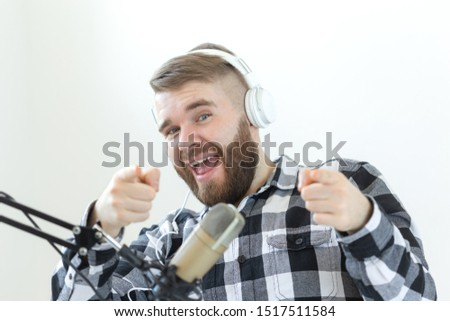 Podcasting, music and radio concept - Happy man with microphone and big headphone #1517511584
