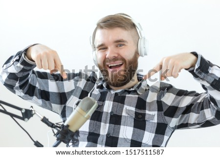 Podcasting, music and radio concept - Happy man with microphone and big headphone #1517511587