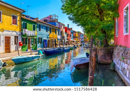 Street with colorful buildings and canal in Burano island, Venice, Italy. Architecture and landmarks of Venice, Venice postcard Royalty-Free Stock Photo #1517586428
