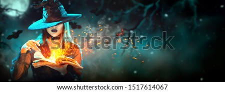 Halloween Witch girl with magic Book of spells portrait. Beautiful young woman in witches hat conjuring, making witchcraft. Over spooky dark magic forest background. Wide Halloween party art design #1517614067