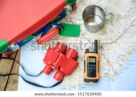 Still life view from above of adventurous objects for kids. Colorful bags, walkie talkie and binoculars over a map, ready for planning a new travel route. Travelling, dream, positive future concept. #1517620400