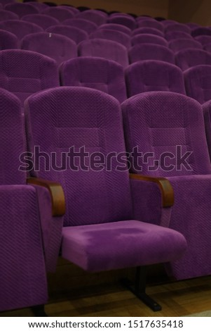 Purple soft velvet chairs in the theater hall #1517635418