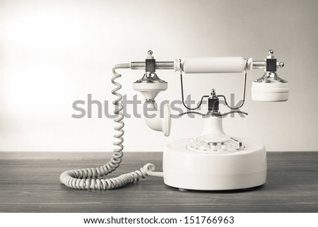 Vintage telephone on wood table black and white photo