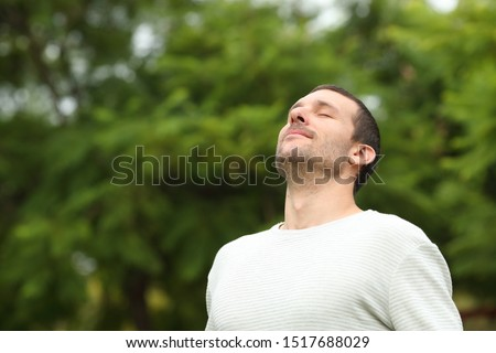 Relaxed adult man breathing fresh air in a forest with green trees in the background #1517688029