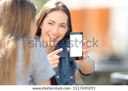Happy girl shows blak smart phone screen to her friend in the street #1517690291