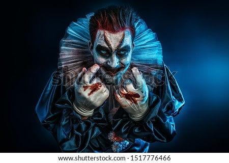 A portrait of an angry crazy clown from a horror film with a hammer. Halloween, carnival.