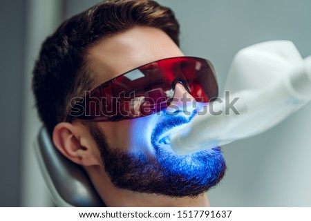 Teeth whitening. Man having teeth whitened by dental UV laser whitening device. Teeth whitening machine,eyes protected with glasses. #1517791637