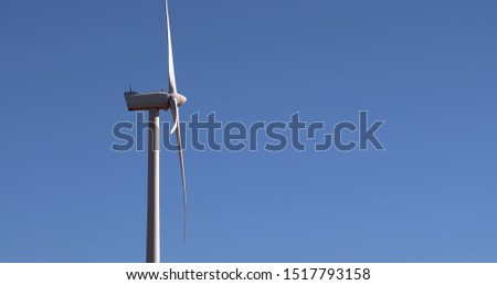 Alternative energy sources. Large blades of wind turbines in rotation with the blue sky in the background, aerial view #1517793158