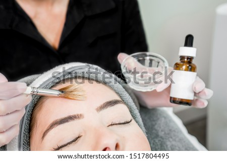 Close up of beautician (cosmetologist) applying chemical peel treatment on patient in a beauty spa, for skin rejuvenation, complexion and acne beauty treatments. #1517804495