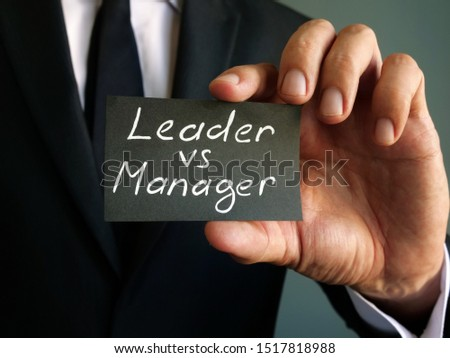 Leader vs manager inscription on a piece of black paper. #1517818988