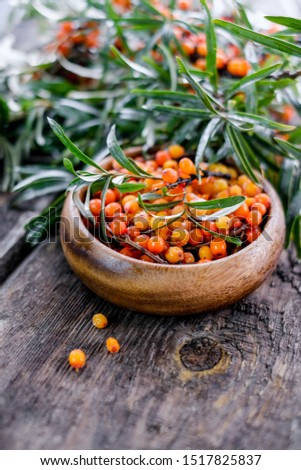 Leaves and berries of orange sea buckthorn on wooden table background #1517825837
