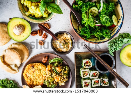 Healthy vegan food table. Flat lay of stew with chickpeas, vegan bergrer, hummus, kale salad, vegan sushi rolls and bread. #1517848883