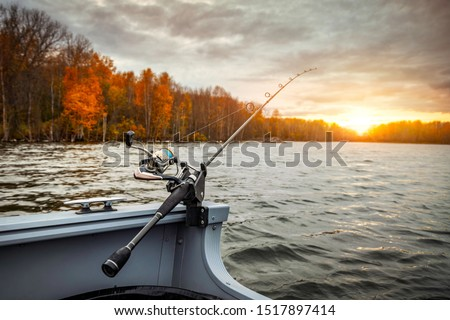 Fishing rod on the boat, sunset time. Beautiful autumn colors. A fishing rod is a long, flexible rod used by fishermen to catch fish.  #1517897414