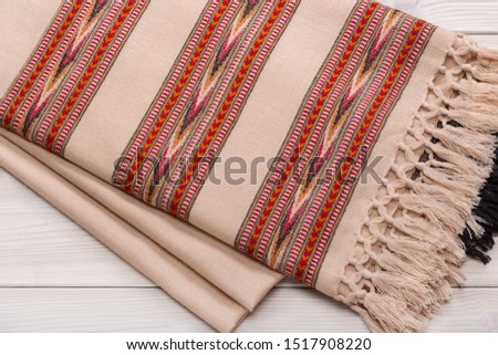 Warm woolen plaid on wooden background. Homeliness. Colorful plaids. #1517908220