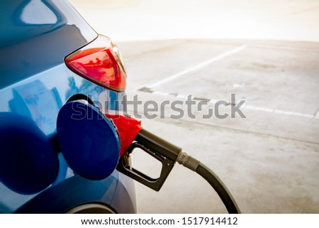 Car fueling at gas station. Refuel fill up with petrol gasoline. Petrol pump filling fuel nozzle in fuel tank of car at gas station. Petrol industry and service. Petrol price and oil crisis concept. #1517914412