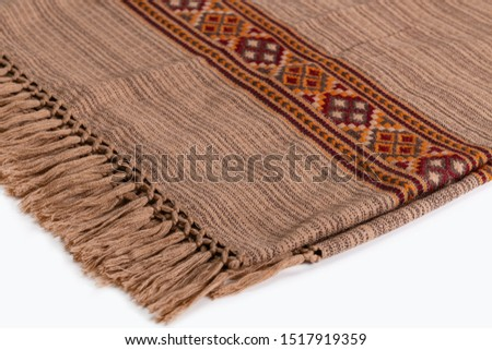 Textile plaid with ornament on wooden background. Colorful plaids, close-up. Homeliness, copy space. #1517919359