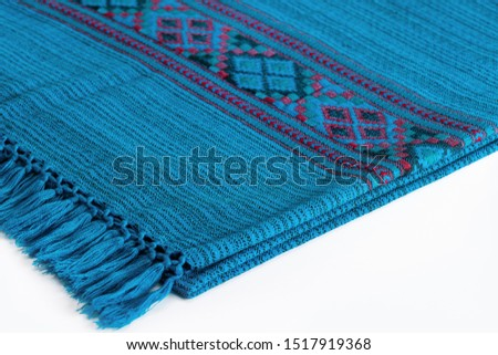 Textile plaid with ornament on wooden background. Colorful plaids, close-up. Homeliness, copy space. #1517919368
