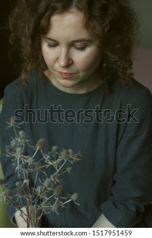 A young curly woman sits in a dark cotton dress in a room holding a dried thistle in her hands.Portrait.sad look #1517951459