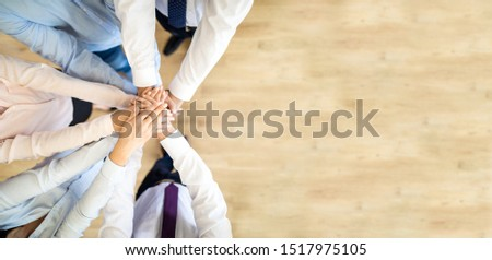Close up top view of young business people putting their hands together. Stack of hands. Unity and teamwork concept. #1517975105