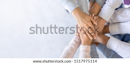 Close up top view of young business people putting their hands together. Stack of hands. Unity and teamwork concept. #1517975114