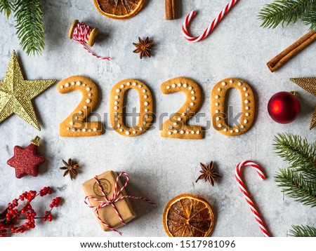 Ginger biscuits of the form of numbers and 2020 new year ginger cookies on grey background. Top view. Seasonal packaging and New Year's attributes  #1517981096