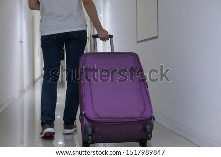 Young woman dragging purple luggage or baggage along the apartment's corridor #1517989847