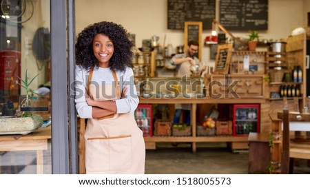 Portrait of a smiling young African American barista leaning with her arms crossed on the door of a trendy cafe  Royalty-Free Stock Photo #1518005573
