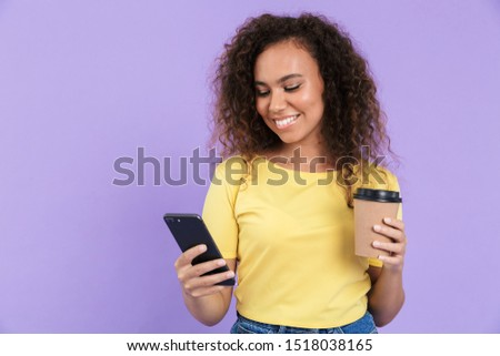 Lovely happy young african girl wearing casual clothing standing isolated over violet background, using mobile phone while drinking coffee to go #1518038165