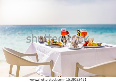 Fresh breakfast in a beautiful location with sea views. Luxury summer vacation or honeymoon destination. Table with gourmet delicious food near the sea with horizon. Beautiful summer breakfast setting #1518052481