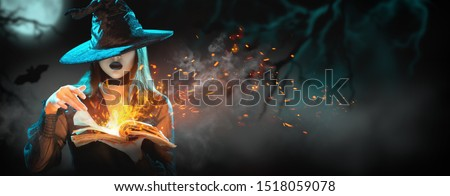 Halloween Witch girl with magic Book of spells portrait. Beautiful young woman in witches hat conjuring, making witchcraft. Over spooky dark magic forest background. Wide Halloween party art design. #1518059078