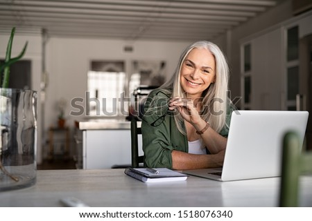 Portrait of happy senior woman holding eyeglasses and looking at camera at home. Successful old lady laughing and working at home. Beautiful stylish elderly woman smiling and relaxing at home. #1518076340