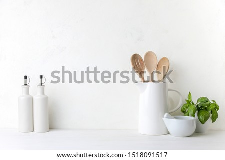 Contemporary kitchen background with kitchen utensils standing on white countertop, blank space for a text, front view Royalty-Free Stock Photo #1518091517