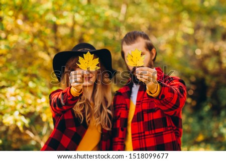 The guy and the girl are holding maple leaves in their hands. couple covers their faces with yellow maple leaves. Stylishly dressed guy and girl. The guy and the girl in red jackets in yellow forest. #1518099677