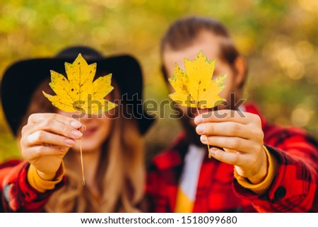 The guy and the girl are holding maple leaves in their hands. couple covers their faces with yellow maple leaves. Stylishly dressed guy and girl. The guy and the girl in red jackets in yellow forest. #1518099680