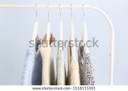 Rack with winter clothes on color background #1518115301