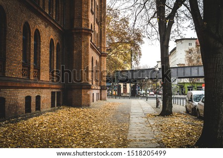 Street in Berlin in autumn.  Autumn street in Berlin with yellow and orange fallen leaves. Autumn cityscape in Berlin. travel and tourism in Berlin concept. #1518205499