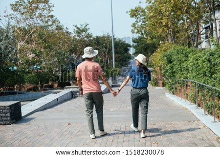 Asian couple wearing a hat holding hand at park. #1518230078
