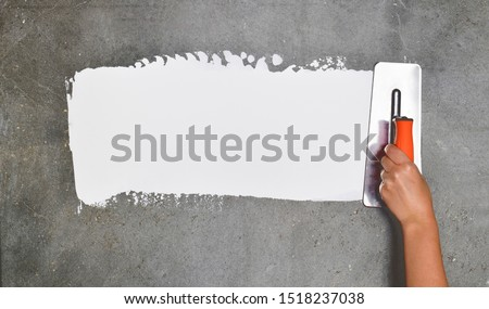 Hand with a spatula, the process of applying a layer of putty. Renovation of apartments. Repair the walls. Free space for advertising, text. #1518237038