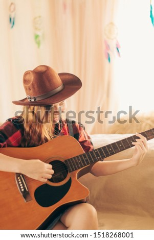Music Concepts. Asian Caucasian girl in countryside playing guitar. Asian women relaxing with music. Asian women have a happy lifestyle.