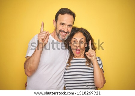 Beautiful middle age couple together standing over isolated yellow background surprised with an idea or question pointing finger with happy face, number one #1518269921