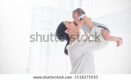 Portrait of asian mother lifting and playing with newborn baby, baby talking to mother. Health care family love together. Asian girl lifestyle. Asia mother's day concept  #1518271010