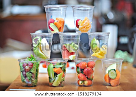 cups of fresh fruits slices - ingredients for smoothie and juice. tasty, fresh and organic #1518279194